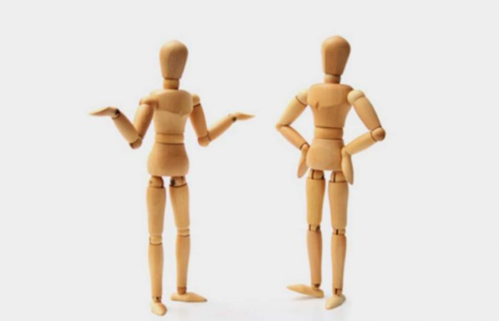 Two wooden marrionettes in different gestures and poses.